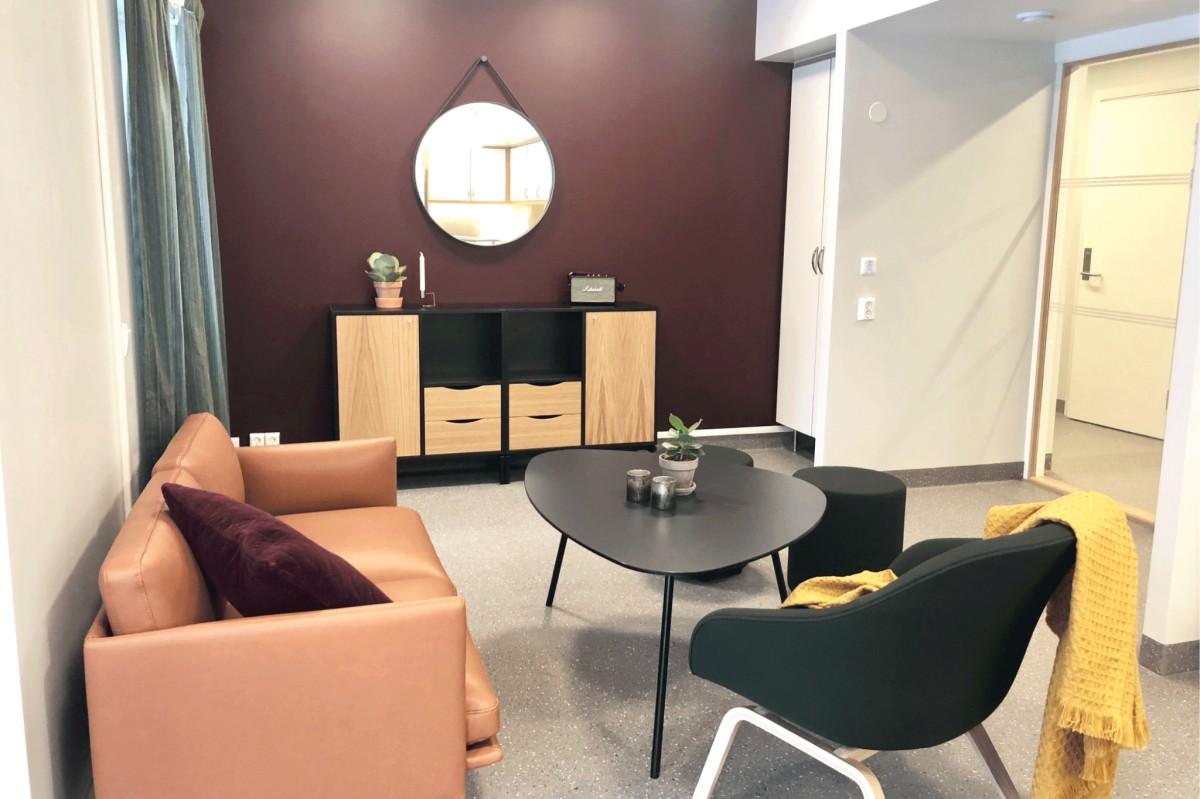 Fellesrommet i kollektivet har to koselige sitteområder med sofa, stoler og puffer